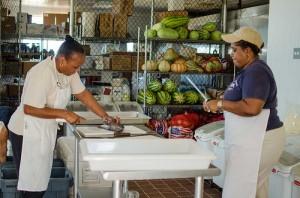 Kitchen ladies filleting tilapia.